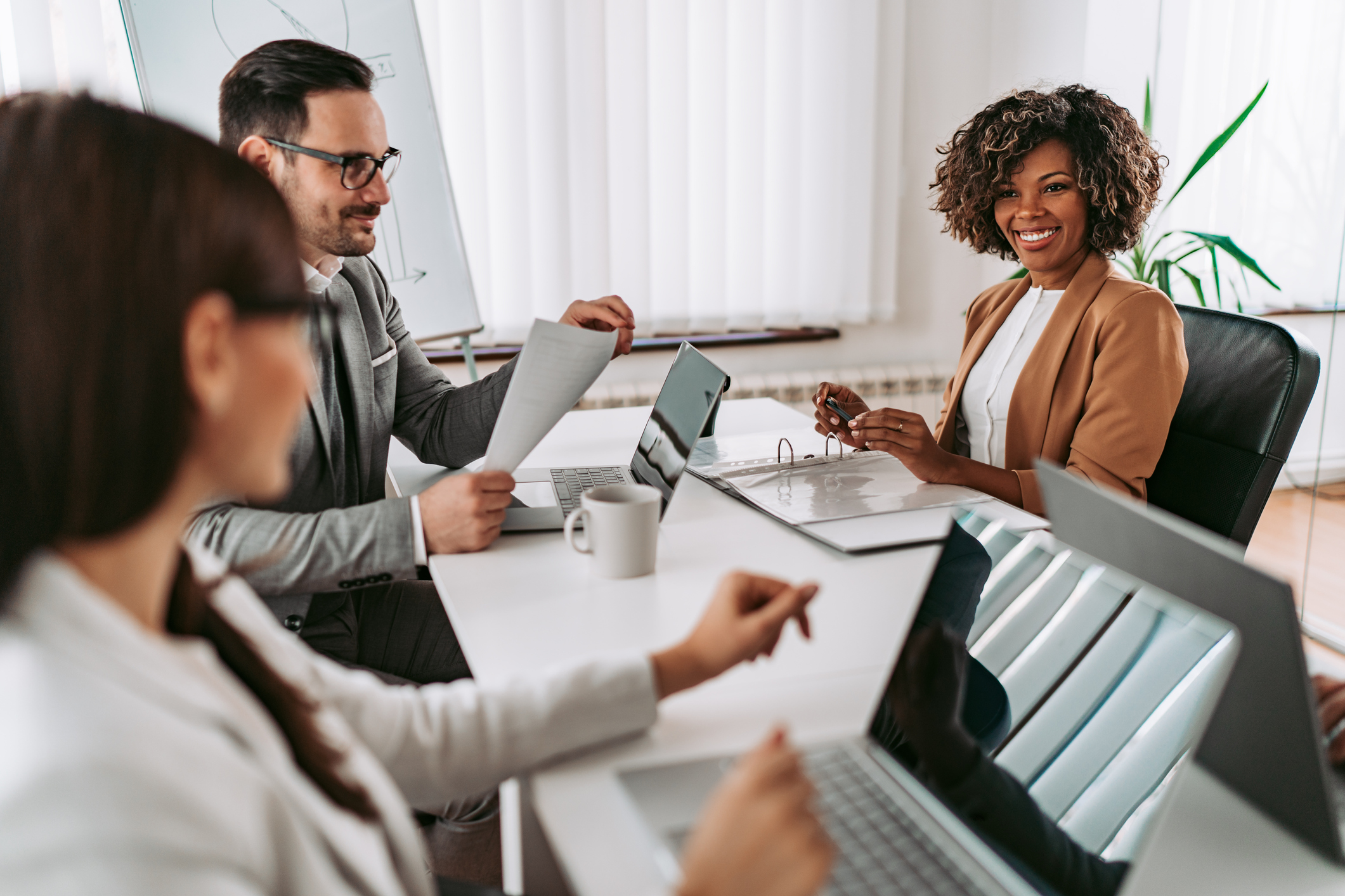 Portrait of cheerful african american businesswoman discussing with colleagues at the meeting and smiling