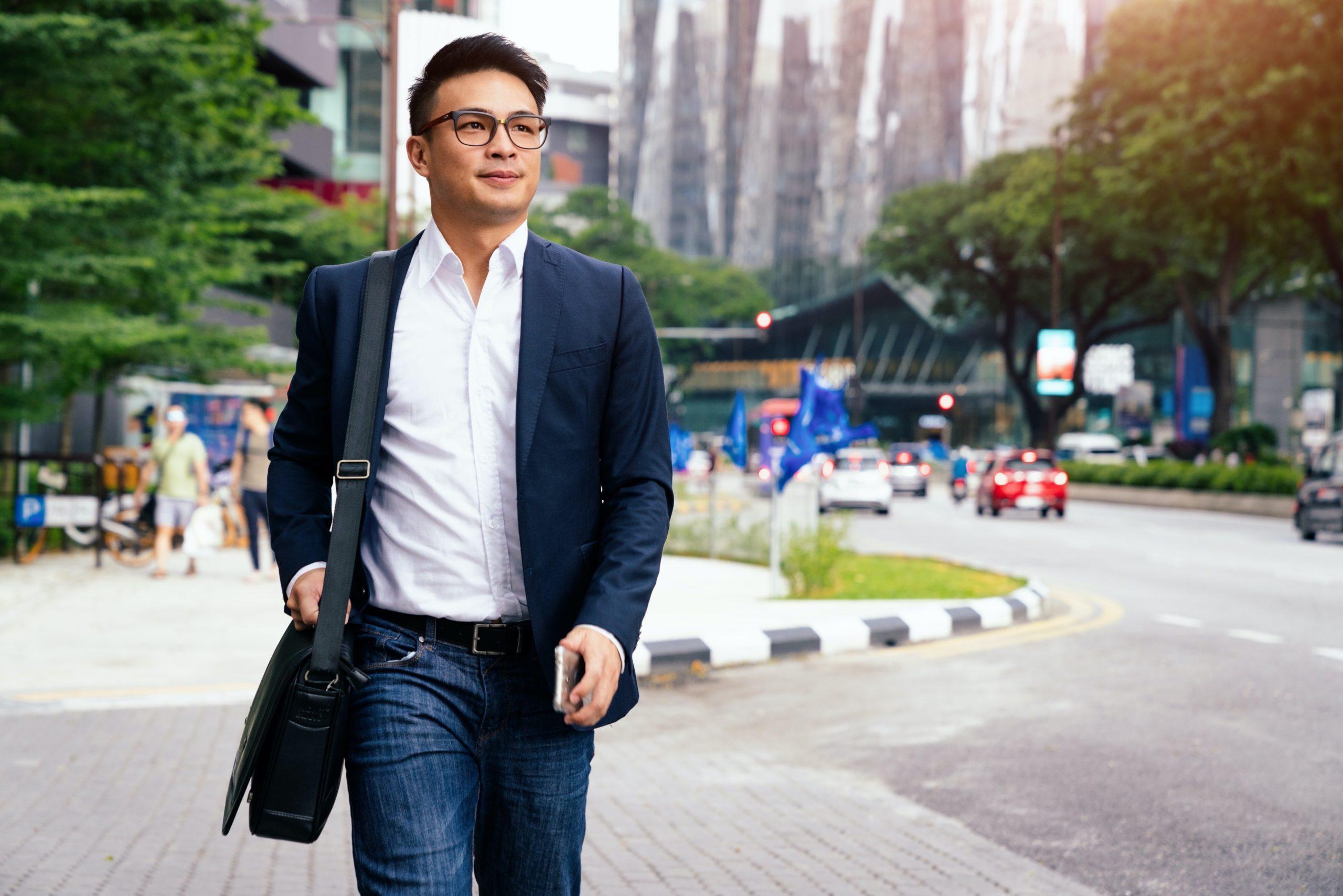 Young chinese businessman walking along the street in downtown Kuala Lumpur. Kuala Lumpur, Malaysia, Asia